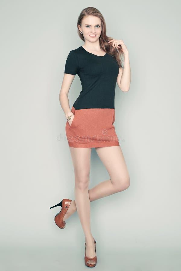 Mode-Modell im schwarzen und hellbraunen Kleiderlächeln lizenzfreie stockfotos