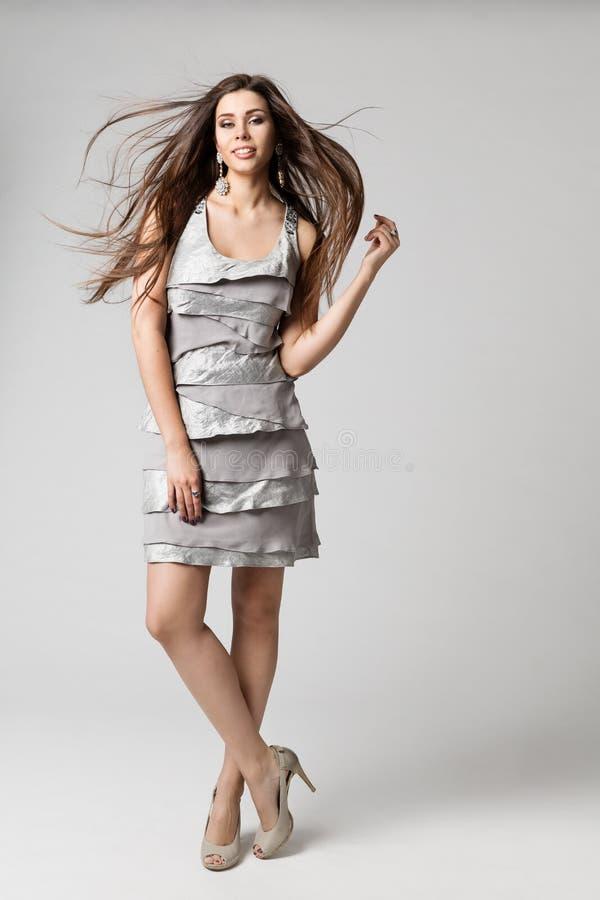 Mode-Modell Long Hair Fluttering auf Wind, silbernes Kleid, Frauen-Studioschönheit Porträt in voller Länge auf Weiß lizenzfreie stockfotos