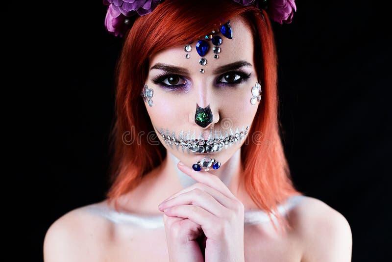 Mode-Modell mit Halloween-Schädelmake-up mit Funkeln und Bergkristallen stockfotos