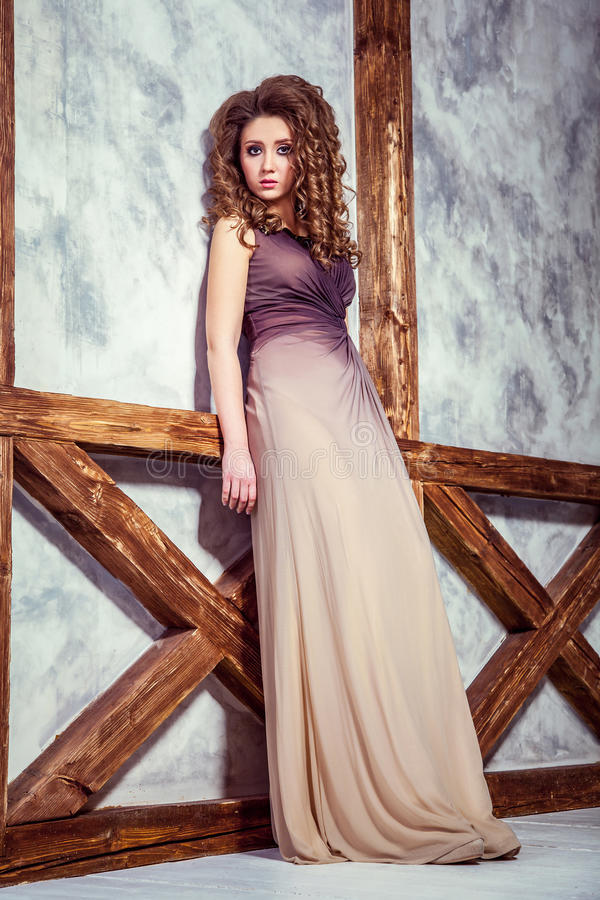 Mode-Modell mit langem Kleid und gelockter Frisur und Make-up, das nahe Wand mit hölzernem Pfosten aufwirft stockfotos