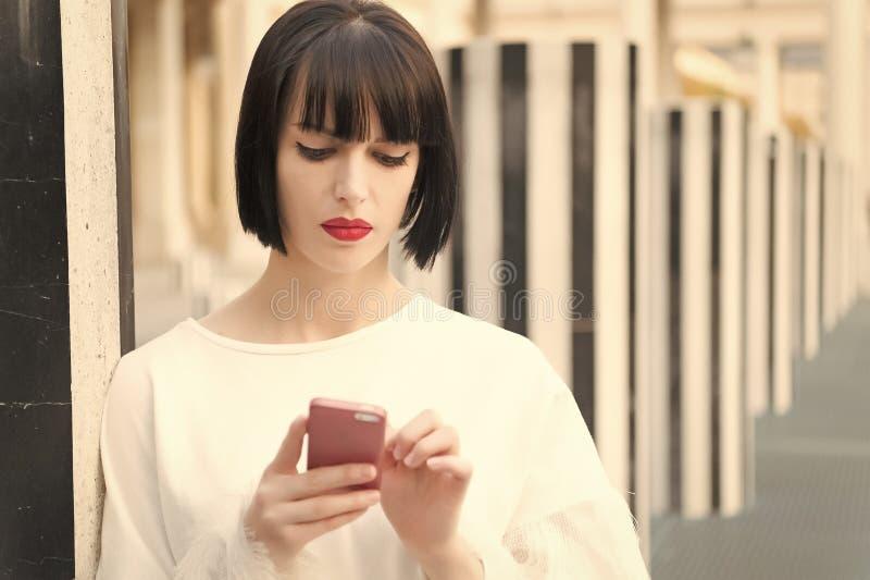 Mode-Modell mit tragbarem Gerät Frau mit rotem Lippengebrauch auf Smartphone in Paris, Frankreich Frau mit Brunettehaargriff lizenzfreie stockbilder