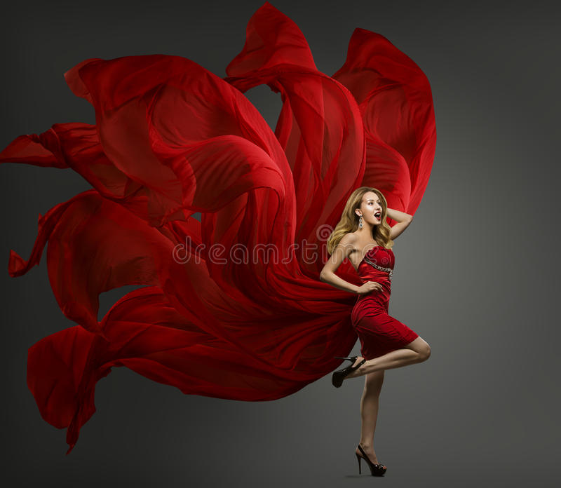 Mode-Modell Red Dress, Frauen-Tanzen im Fliegen-Gewebe-Kleid stockfotografie