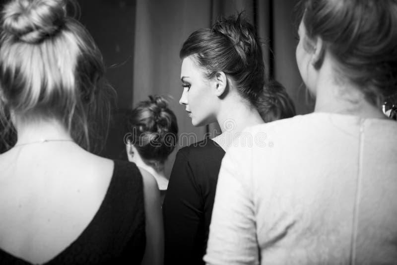 Mode-Modelle vorbereitet für Rollbahn vom stilvollen Designer Mädchen versteckt sich im Hemd eines Mannes stockbild