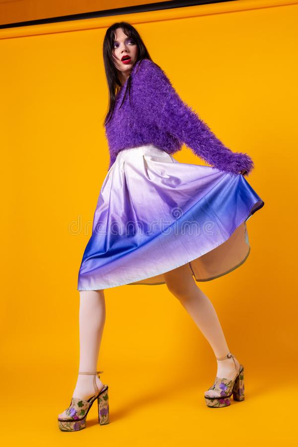 Mode modellerar den fulla längdståenden för flickan som isoleras på orange bakgrund royaltyfria bilder