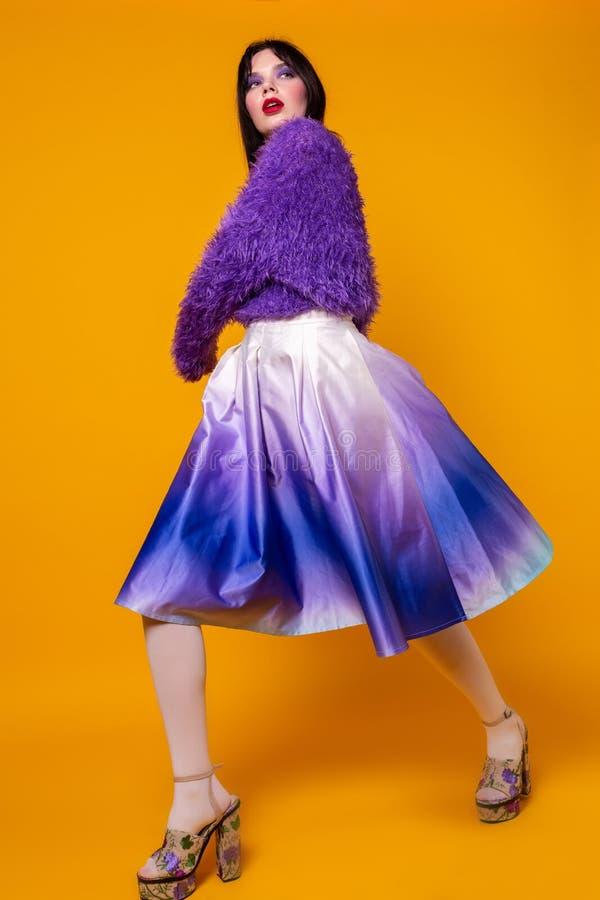 Mode modellerar den fulla längdståenden för flickan som isoleras på orange bakgrund arkivbild