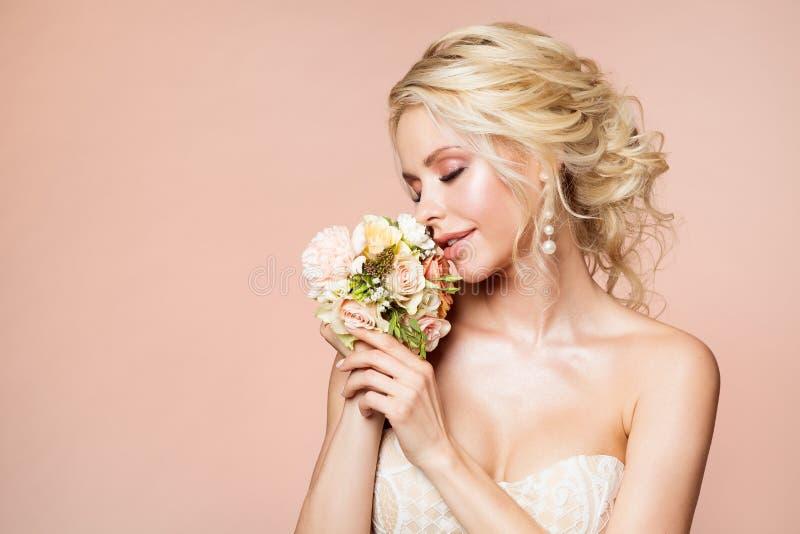 Mode modellerar skönhetståenden, kvinnan som luktar blommabuketten, härlig makeup och frisyren, flickastudioskott på beiga arkivbild