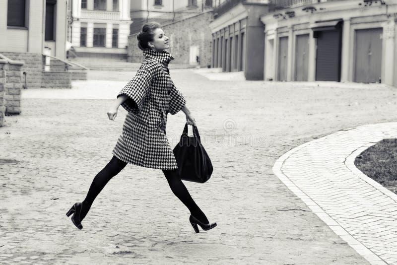 Mode och folkbegrepp - lycklig ung kvinna eller spring och banhoppning för tonårs- flicka som är höga på stadsgatan royaltyfri fotografi