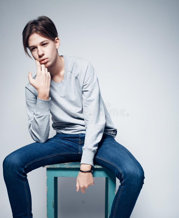 Mode och folkbegrepp: stilfull moderiktig iklädd tillfällig kläder för ung man som poserar i över grå bakgrund royaltyfri foto