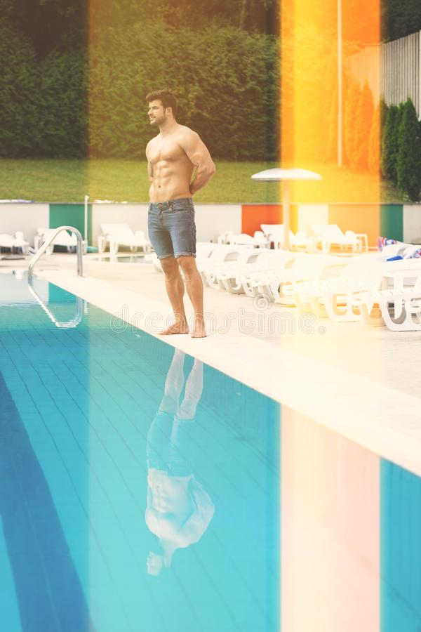 Mode-Portr?t eines sehr muskul?sen Mannes in den kurzen Jeans am Swimmingpool lizenzfreies stockbild