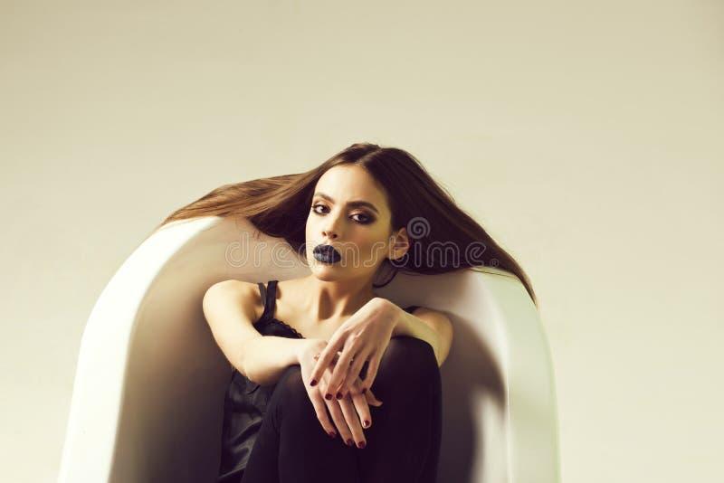 Mode portrai einer Frau in der Badewanne weiße Badewanne und schöne junge Frau mit den schwarzen Lippen lizenzfreies stockfoto