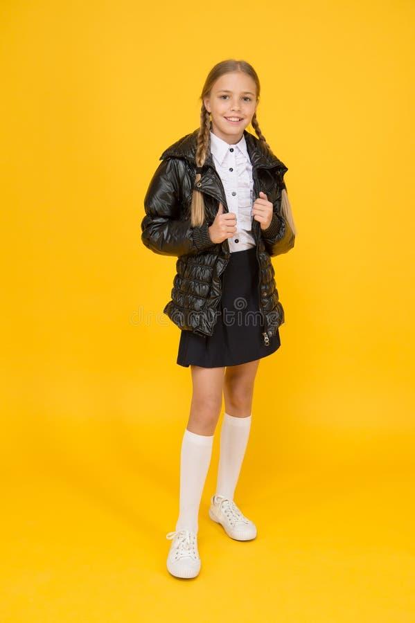 Mode-shop Kute girl draagt zwarte jas op gele achtergrond Mode-concept Kleding kopen voor schoolseizoen stock foto's