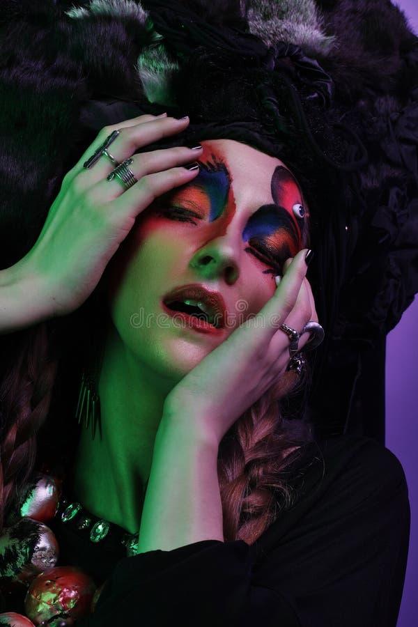 Mode, skönhet, folk och halloween begrepp: Ung kvinna med ett ljust idérikt smink och en stor svart huvudbonad arkivfoton