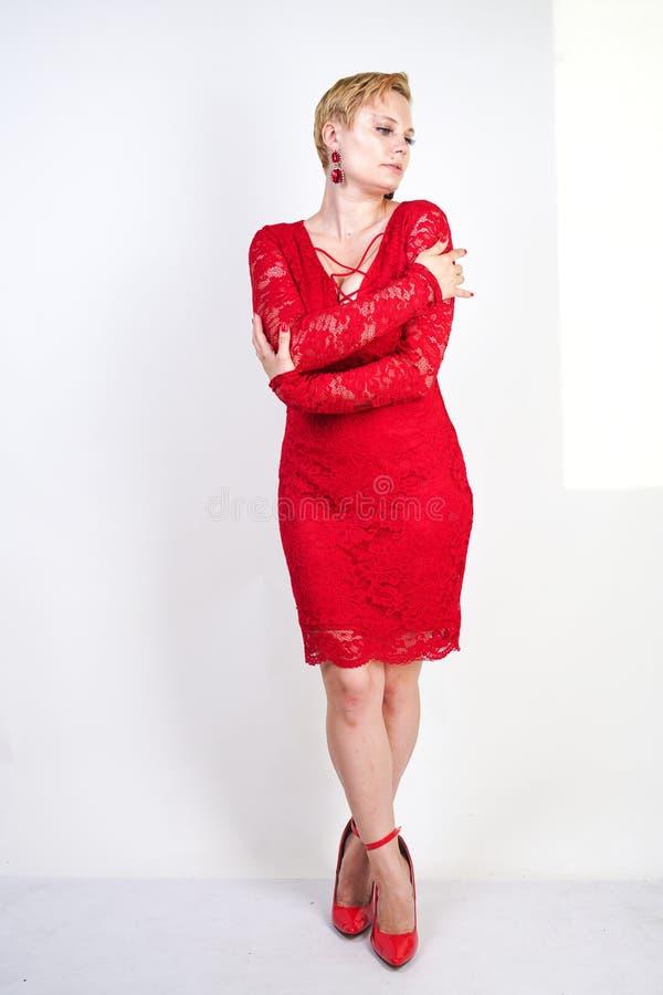Mode som är kvinnligt i rött, snör åt klänningen som bara står plus blond kvinna för format med kort hår och den knubbiga kroppen arkivfoton