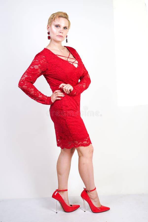 Mode som är kvinnligt i rött, snör åt klänningen som bara står plus blond kvinna för format med kort hår och den knubbiga kroppen royaltyfria bilder