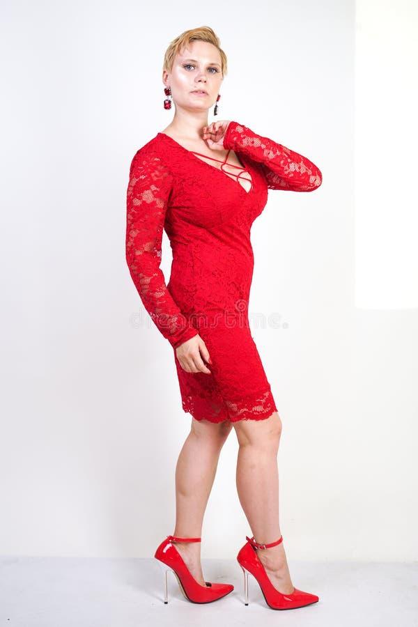 Mode som är kvinnligt i rött, snör åt klänningen som bara står plus blond kvinna för format med kort hår och den knubbiga kroppen arkivfoto