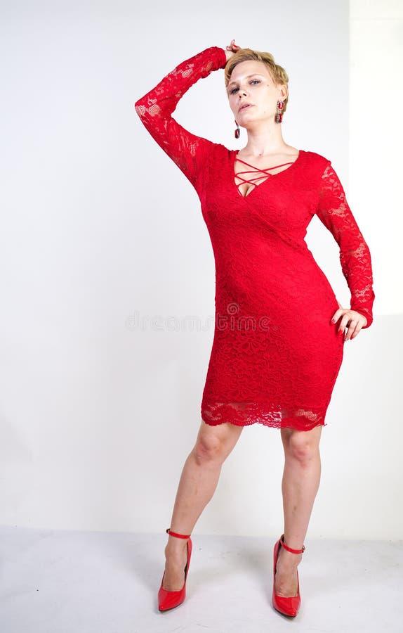 Mode som är kvinnligt i rött, snör åt klänningen som bara står plus blond kvinna för format med kort hår och den knubbiga kroppen arkivbild