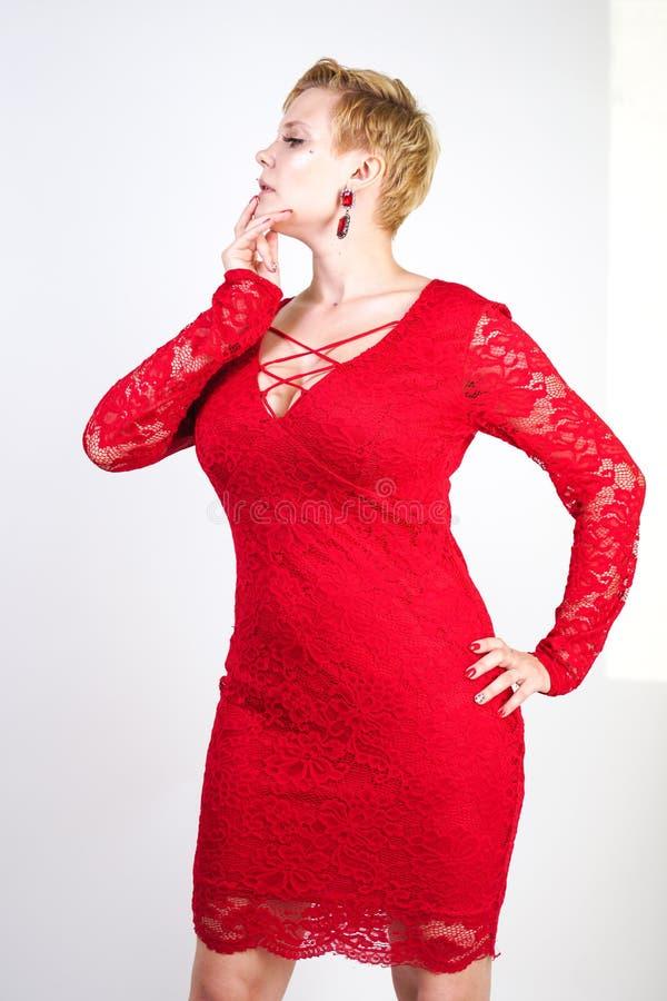 Mode som är kvinnligt i rött, snör åt klänningen som bara står plus blond kvinna för format med kort hår och den knubbiga kroppen royaltyfri foto