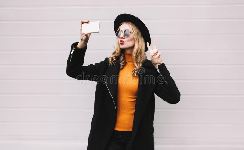 Mode, teknologi och folkbegrepp - kall flicka som tar selfiebilden vid smartphonen, arkivfoton