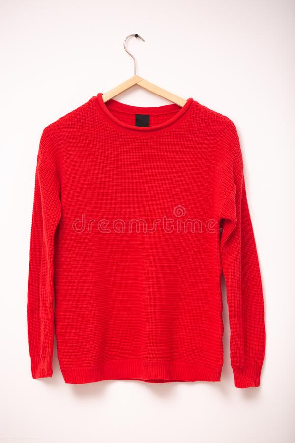 Mode und Kleidungskonzept Rote gestrickte warme Strickjacke der Frau auf Aufhängern gegen weißen Hintergrund Vertikaler Schuss lizenzfreies stockfoto
