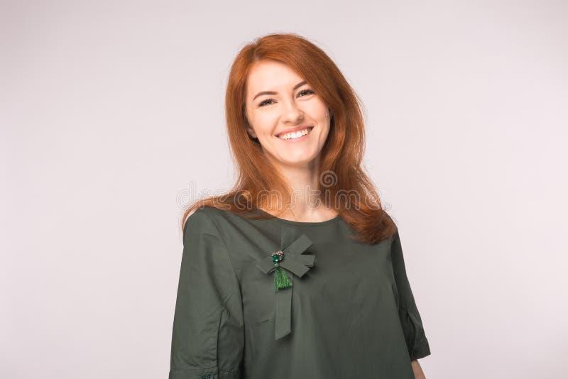 Mode und Leutekonzept - Porträt der glücklichen Ingwerfrau, die Kamera über weißem Hintergrund betrachtend lächelt stockbilder