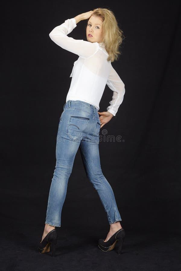 Mode - ung kvinna med blusen och jeans som visar bak royaltyfri fotografi