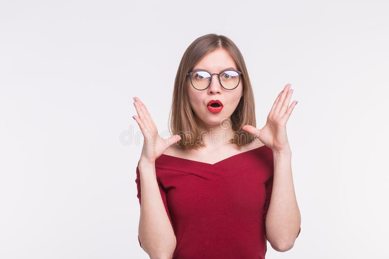 Mode, uttryck och folkbegrepp - den unga kvinnan i exponeringsglas förvånade och satte hennes händer upp på vit bakgrund royaltyfri fotografi