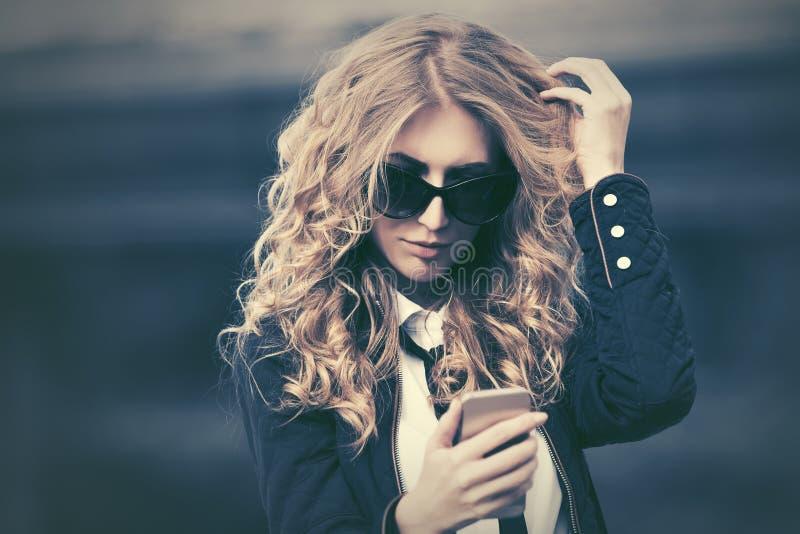 Modeaffärskvinna i solglasögon genom att använda den smarta telefonen i stadsgata fotografering för bildbyråer