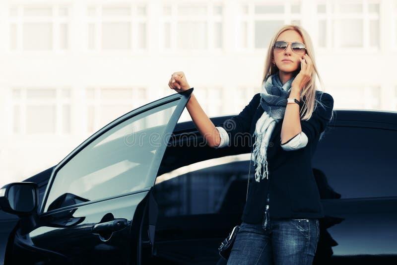 Modeaffärskvinna i solglasögon som talar på mobiltelefonen bredvid en hennes bil arkivbild