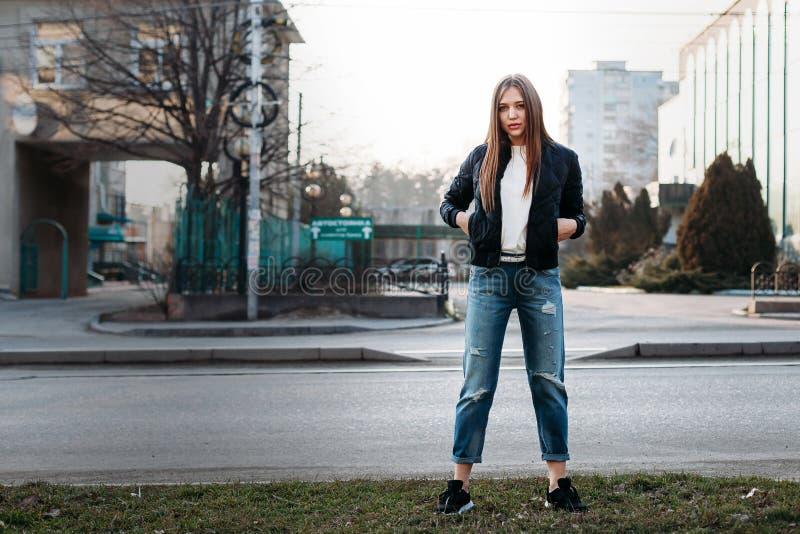 Modeartporträt des jungen modischen Mädchens, das entlang der Straße aufwirft Tragendes T-Shirt und Lederjacke des Mädchens, die  stockbilder