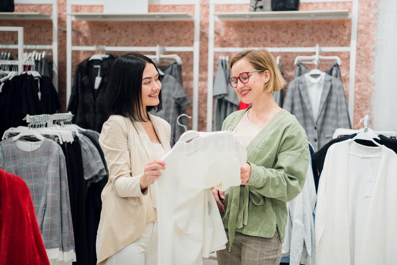Modeberater, der dem Kunden Kleidung zeigt stockbild