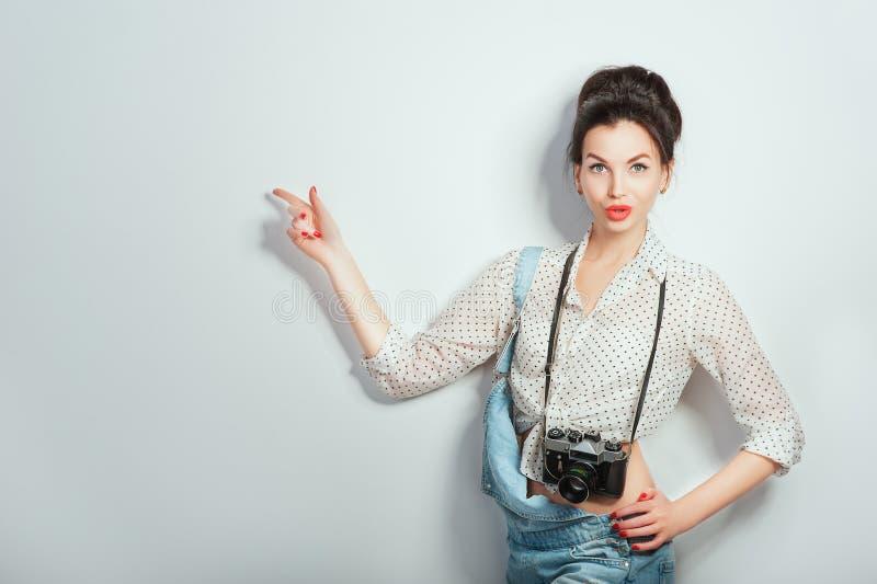 Modeblick, n?tt kall modell f?r ung kvinna med den retro kameran som b?r i grov bomullstvillkl?der som pekar p? kopieringsutrymme royaltyfri fotografi
