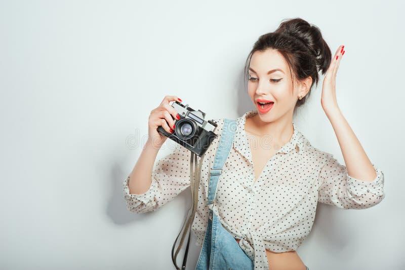 Modeblick, n?tt kall modell f?r ung kvinna med den retro kameran som b?r i grov bomullstvillkl?der som poserar p? den vita v?ggen arkivfoto