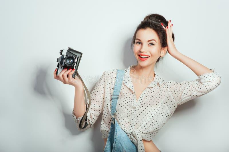 Modeblick, n?tt kall modell f?r ung kvinna med den retro kameran som b?r i grov bomullstvillkl?der som poserar p? den vita v?ggen arkivfoton