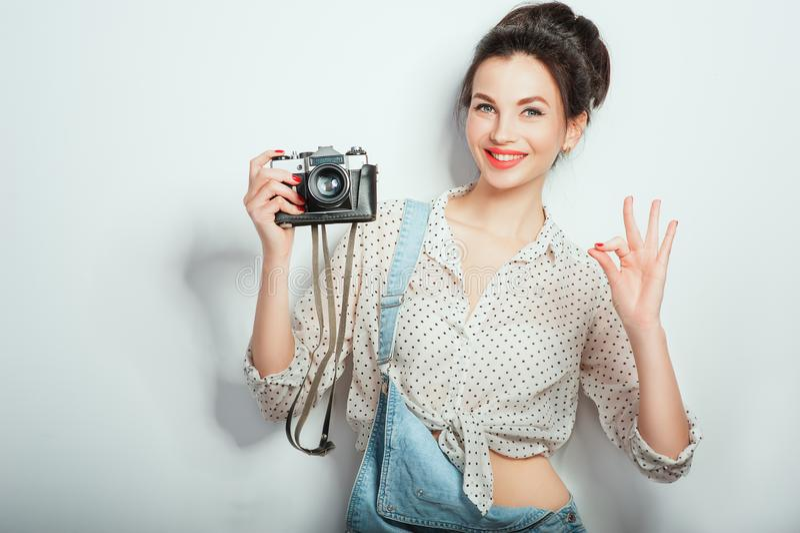 Modeblick, n?tt kall modell f?r ung kvinna med den retro kameran som b?r i grov bomullstvillkl?der som poserar p? den vita v?ggen arkivbild