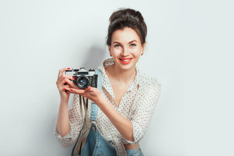 Modeblick, n?tt kall modell f?r ung kvinna med den retro kameran som b?r i grov bomullstvillkl?der som poserar p? den vita v?ggen royaltyfri bild