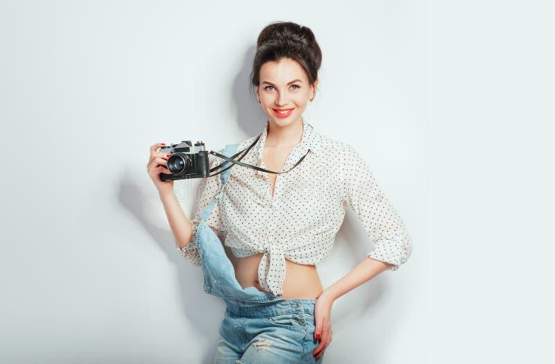 Modeblick, n?tt kall modell f?r ung kvinna med den retro kameran som b?r i grov bomullstvillkl?der som poserar p? den vita v?ggen royaltyfri fotografi