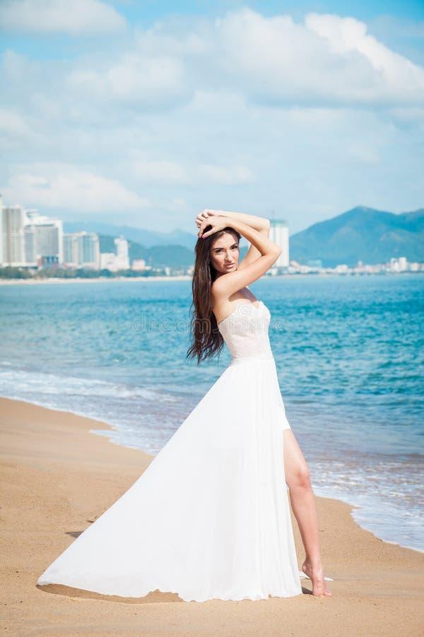 Modebrud som går ner havskusten i en vit klänning Den härliga flickan går barfota down stranden bröllop för tappning för klädpard arkivfoton
