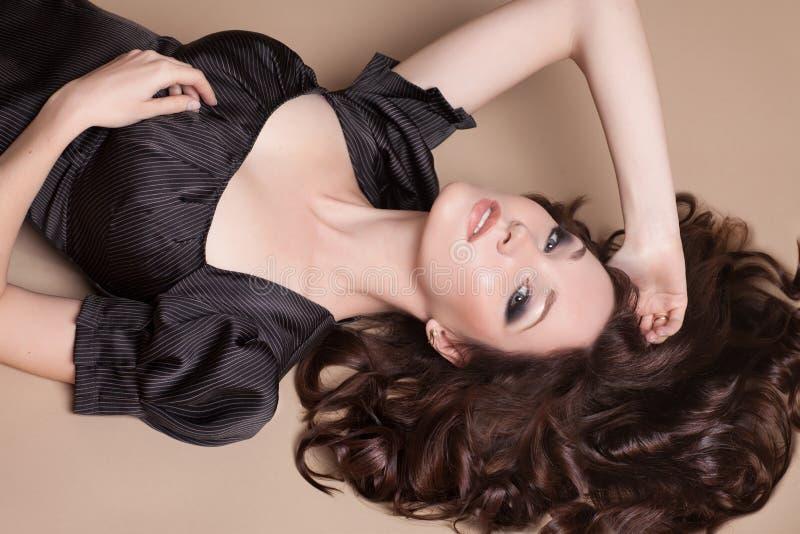 Modebrunettkvinna med den bruna flickan för lockigt hår med perfekt hud och makeup. Retro skönhetmodell arkivbild