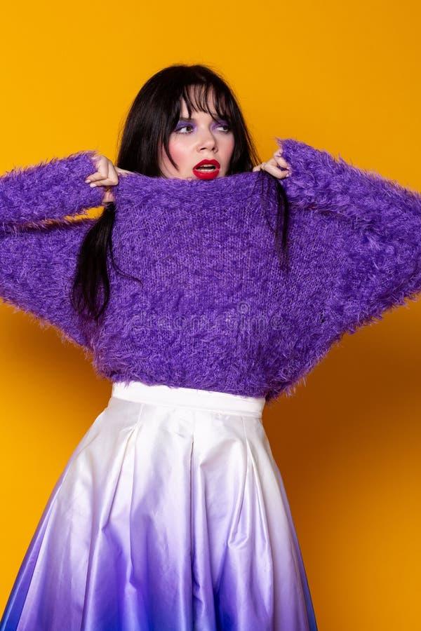 Modebrunettmodell i purpurfärgad tröja och kjolen som poserar i studion royaltyfria foton
