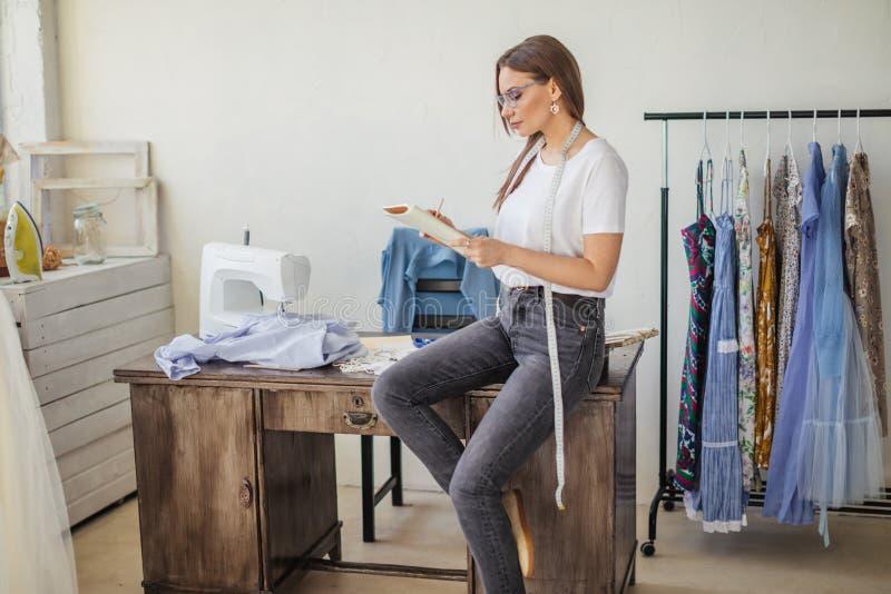 Modedesigner bei der Arbeit Talanted-Damenschneiderin-Zeichnungsskizze an ihrem Arbeitsplatz lizenzfreie stockfotografie