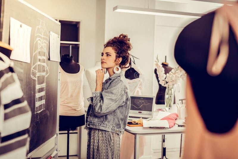 Modedesigner, der an das Redigieren ihrer Skizzen denkt stockfotos