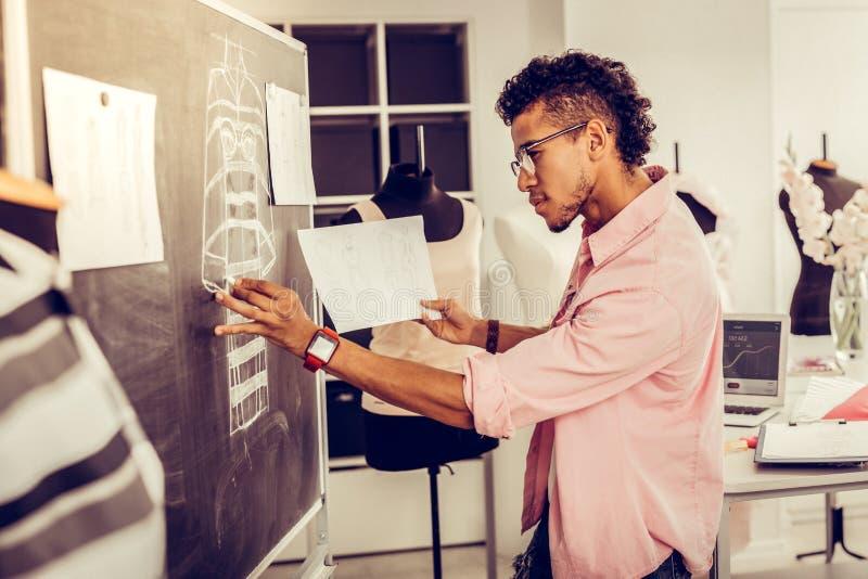 Modedesigner, der seine Skizze auf einer Tafel neu entwirft lizenzfreies stockbild