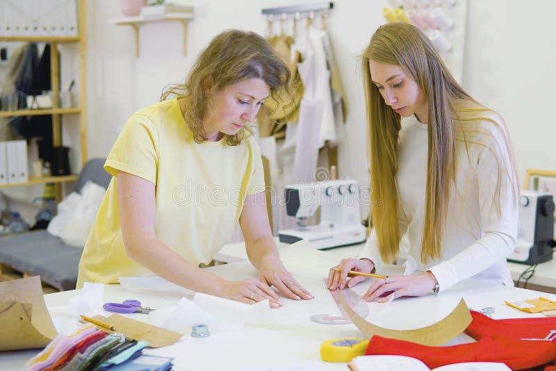 Modedesigner, die im Salon für nähende Brautkleider arbeiten lizenzfreie stockbilder
