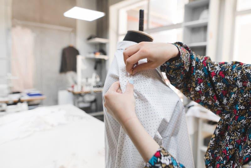 Modedesigner fügt Nadeln in die Kleidung einer Attrappe ein Schaffung von Modekleidung im Studio lizenzfreies stockfoto