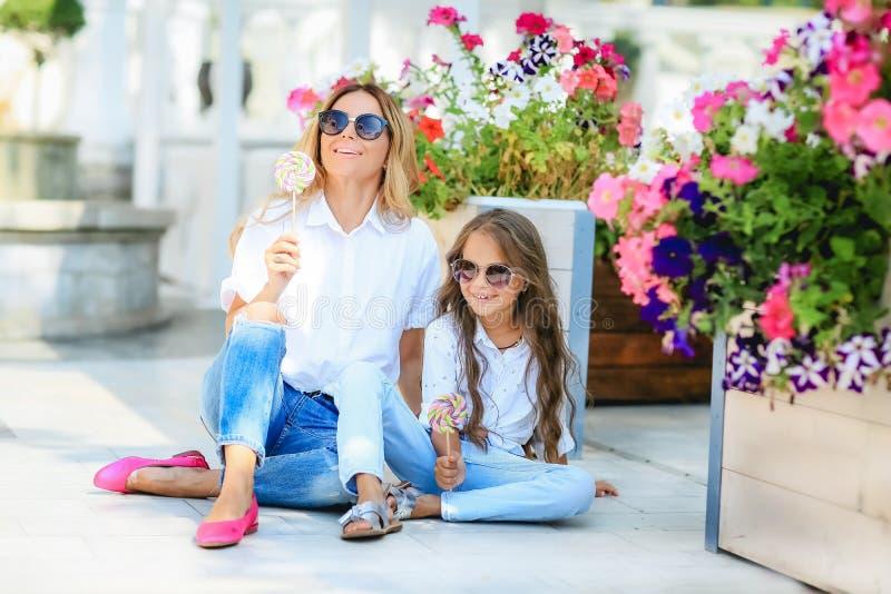 Modefamilienkonzept - stilvolle Mutter und Kind tragen Ein Porträt einer glücklichen Familie: eine junge Schönheit mit ihr lizenzfreie stockfotografie