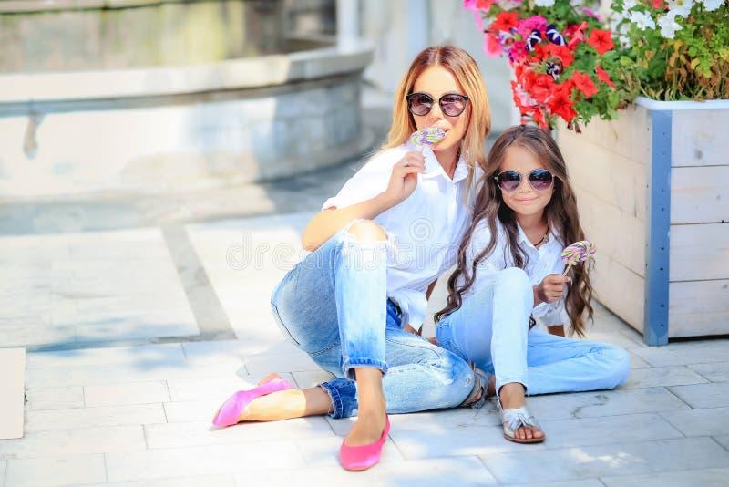 Modefamilienkonzept - stilvolle Mutter und Kind tragen Ein Porträt einer glücklichen Familie: eine junge Schönheit mit ihr stockfotografie
