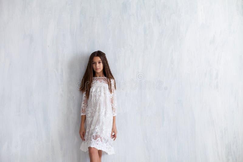 Modeflicka 12 gamla år i en vit klänning royaltyfria bilder