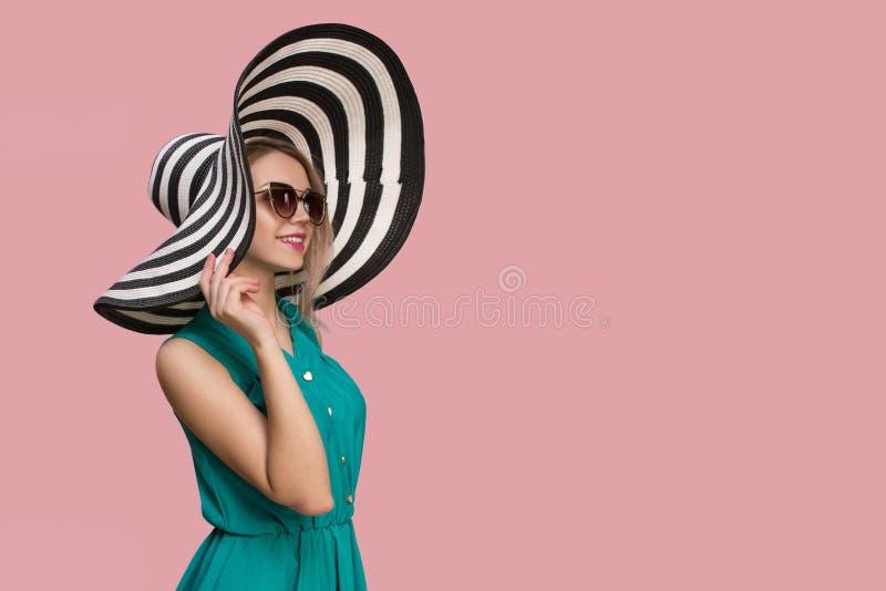 Modeflicka i en stor hatt och solglasögon på en kulör bakgrund royaltyfria foton