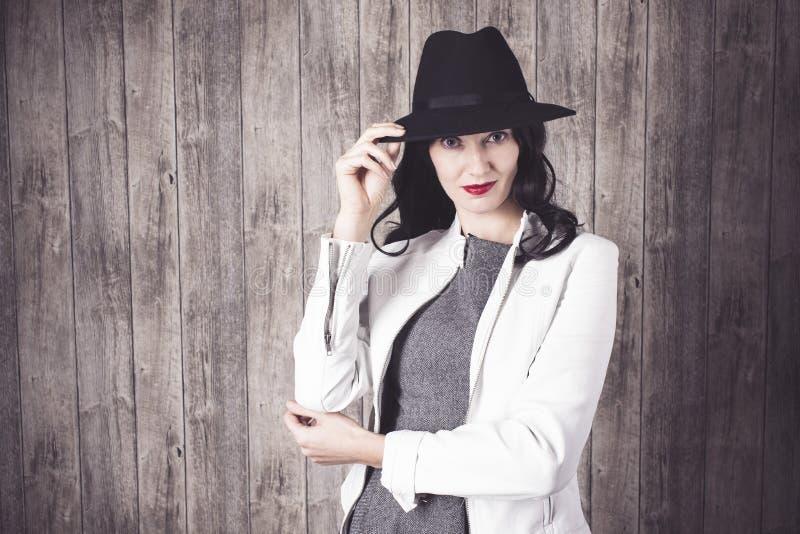 Modeflicka i grå färgklänning och hatt royaltyfri foto