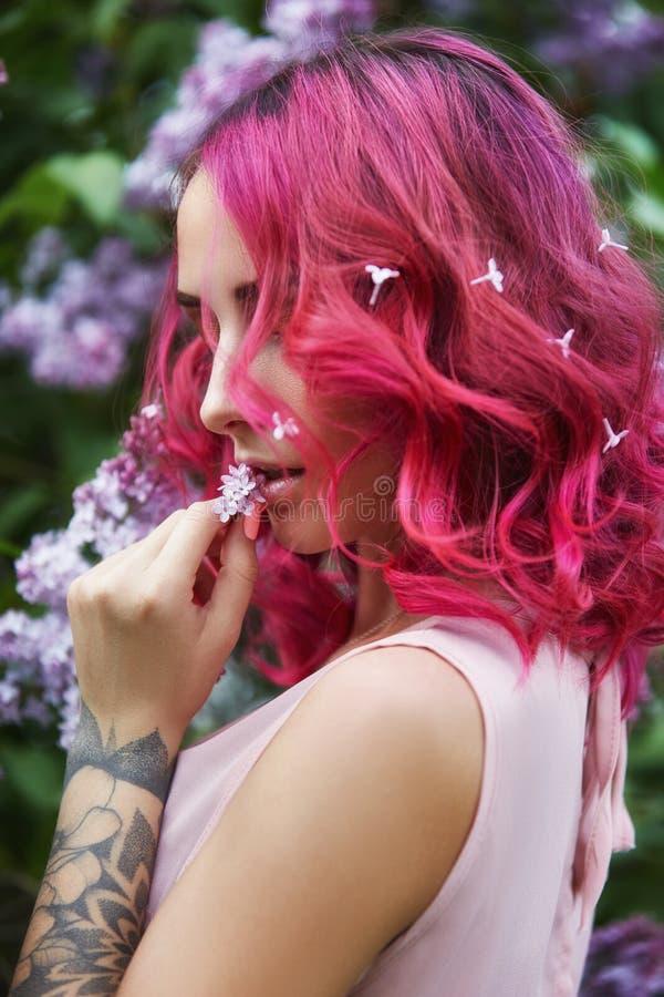 Modeflicka med rött hår och stor hattkall, vårstående i lila färger i sommar Härlig röd rosa klänning, tatueringar på arkivfoton